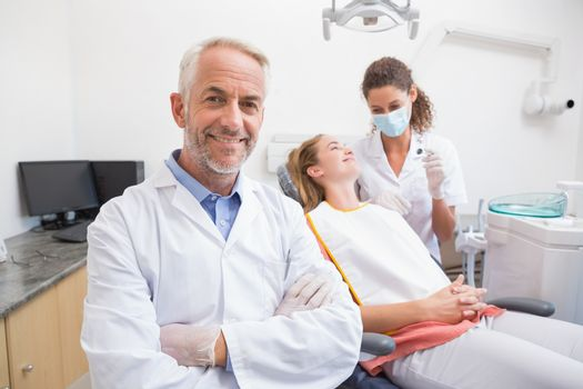 Dentist smiling at camera with assistant and patient behind at the dental clinic