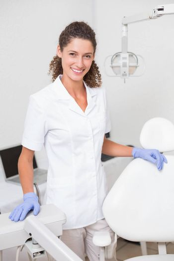Dental assistant smiling at camera beside chair at the dental clinic