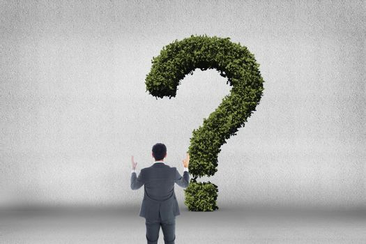 Businessman looking at question mark made of bushes