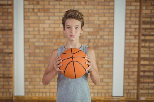 Determined boy holding a basketball