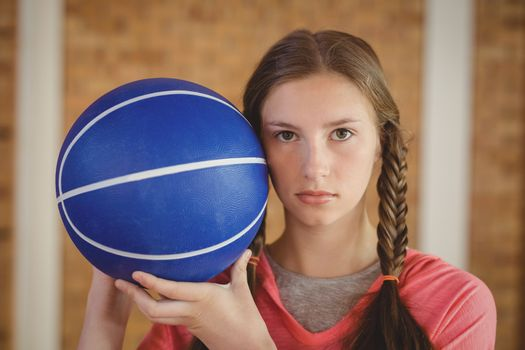 Determined girl holding a basketball