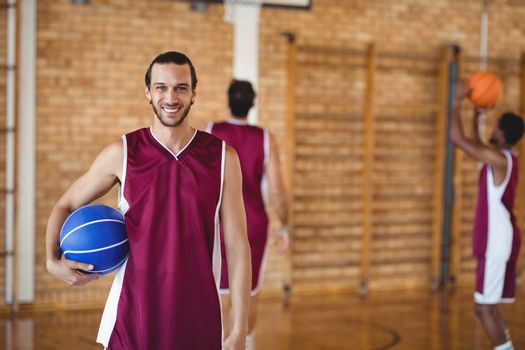 Smiling basketball player holding a basketball