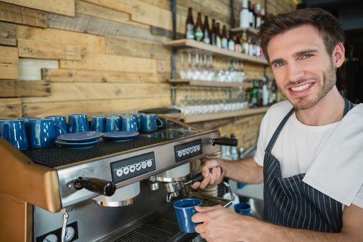 Portrait of smiling waiter preparing coffee from coffee machine