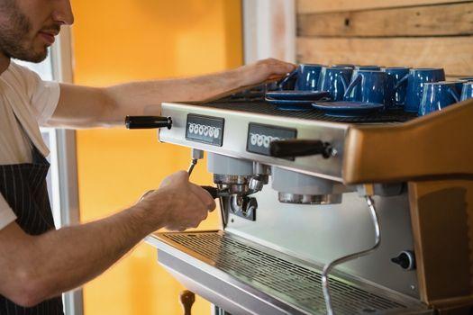 Waiter preparing coffee from coffee machine