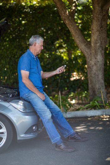 Man looking at mobile phone after car breakdown