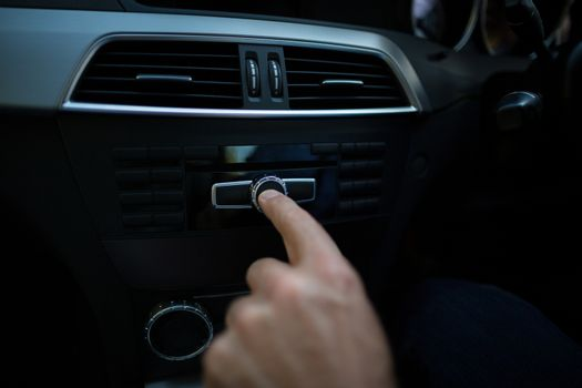 Cropped hand adjusting volume in car