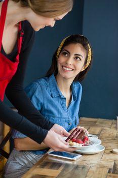 Smiling owner serving sweet food