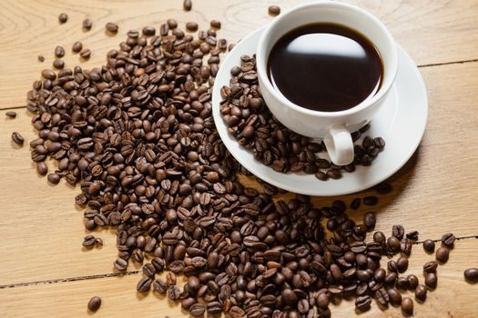 Coffee beans with cup and saucer on table