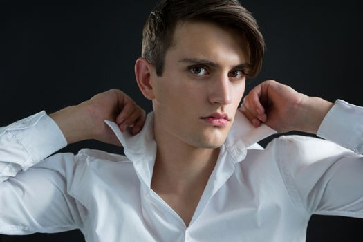 Androgynous man adjusting his collar against black background
