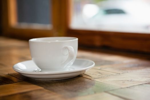 Close up of cup and saucer on wooden table