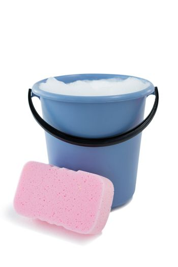 Close up of sponge by bucket containing soap sud