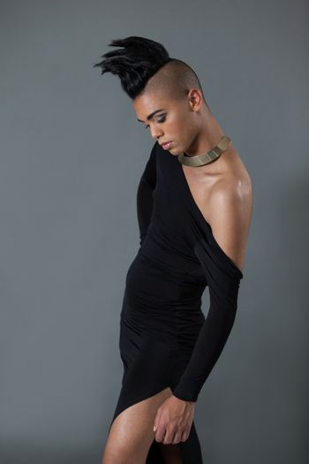 Transgender with half shaved hairstyle against gray background