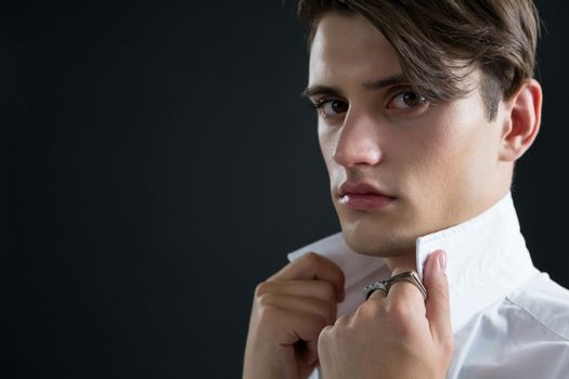 Androgynous man holding his collar against black background