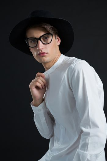 Androgynous man in hat posing with hand on collar