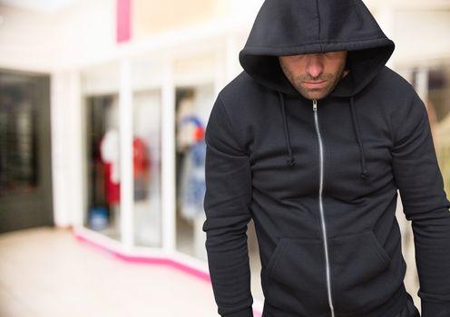 Criminal in hood in supermarket