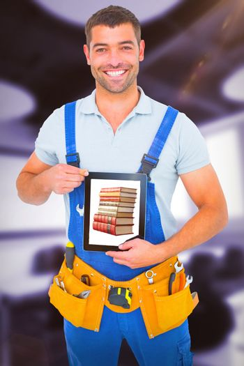 Composite image of happy repairman in overalls holding digital tablet