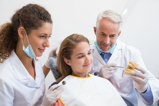 Dentist examining a patients teeth in the dentists chair with assistant at the dental clinic