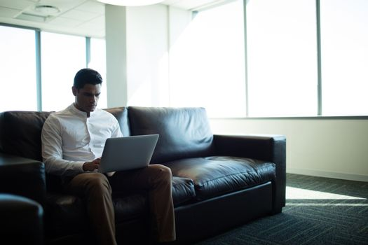 Well dressed businessman using laptop in office