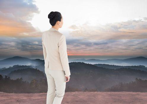 Businesswoman overlooking mountains landscape