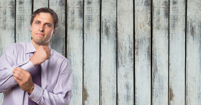Confident businessman adjusting sleeve against wooden wall