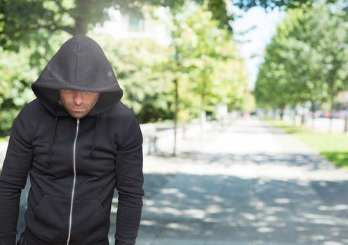 Criminal in hood in front of park