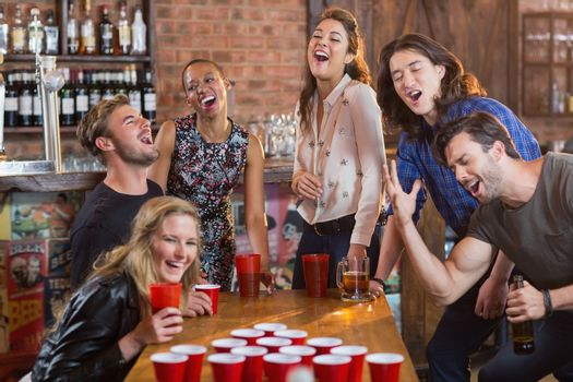 Friends playing beer pong on table
