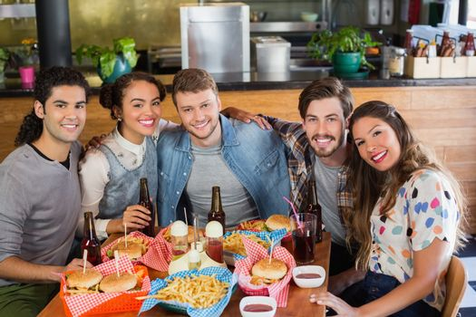 Portrait of happy friends sitting by food and drink served on table in restaurant