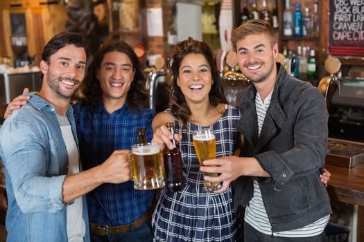 Portrait of friends tossing beer glasses and bottles in pub