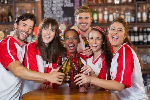 Friends toasting beer bottles in pub