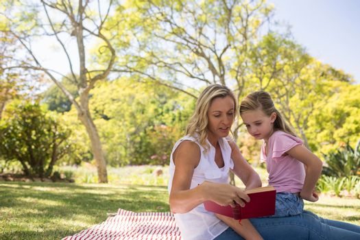 Mother and daughter reading novel in park