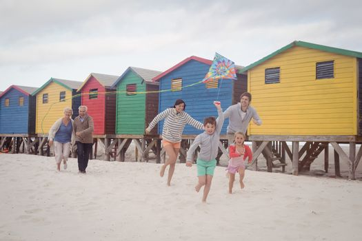 Happy multi-generation family running by beach huts at beach