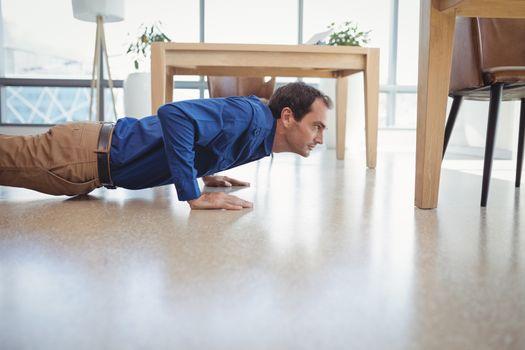 Determined executive doing push-ups