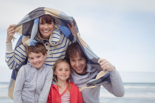 Portrait of smiling family at beach during winter