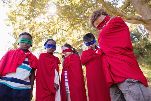 Friends in superhero costumes standing at campsite