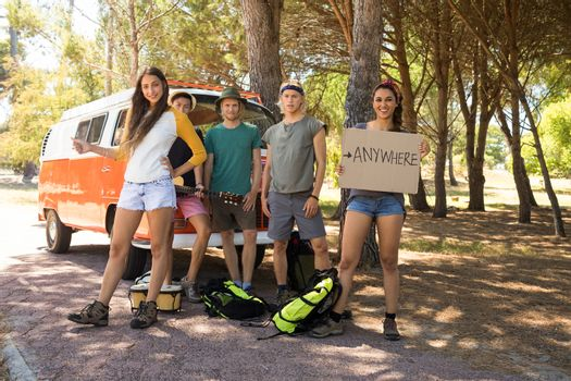 Friends hitchhiking while standing by camper van