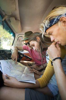 Friends reading map in camper van