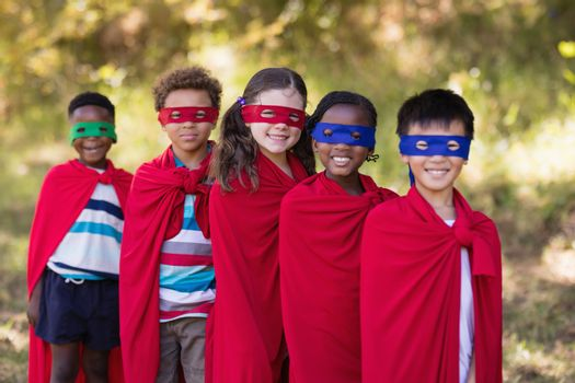 Friends in red superhero costumes standing at campsite