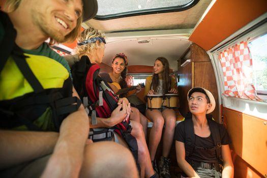Smiling friends enjoying in camper van