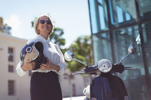 Businesswoman with helmet by motor scooter