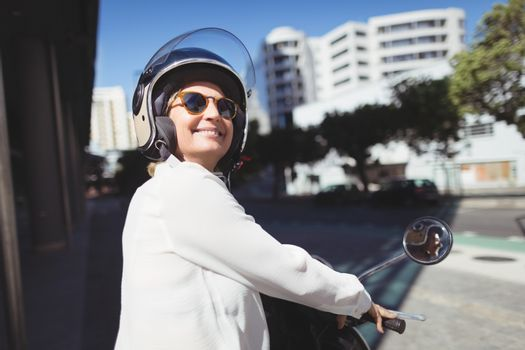 Smiling businesswoman sitting on motor scooter