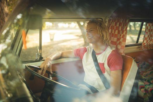 Smiling man sitting in camper van