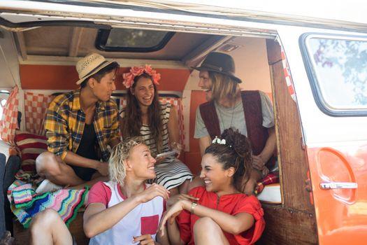 Cheerful friends sitting in camper van