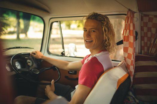 Portrait of man driving camper van