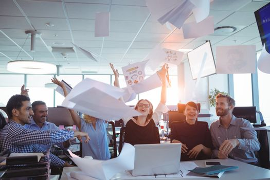 Happy business people tossing papers in air