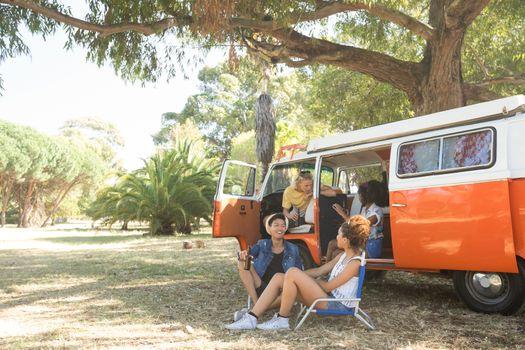 Friend sitting by camper van at campsite