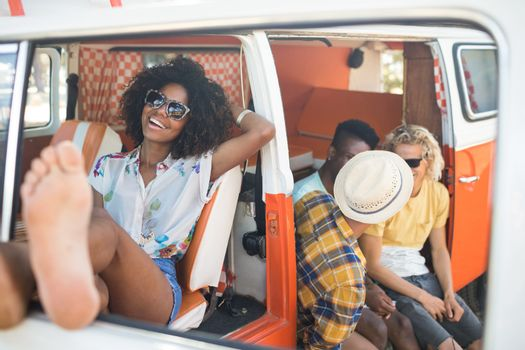 Happy woman relaxing in camper van