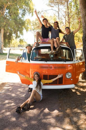 Cheerful friends with camper van on road