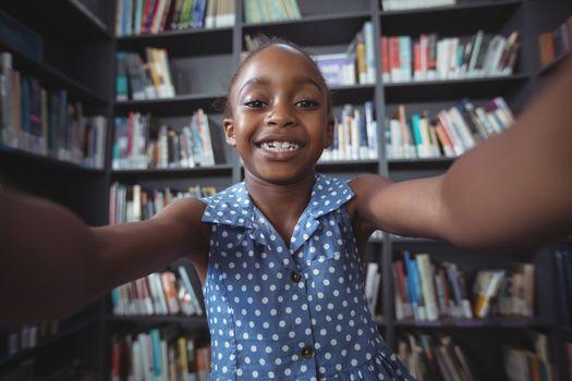 Happy girl against bookshelf in library