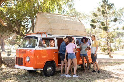 Full length of friends by camper van