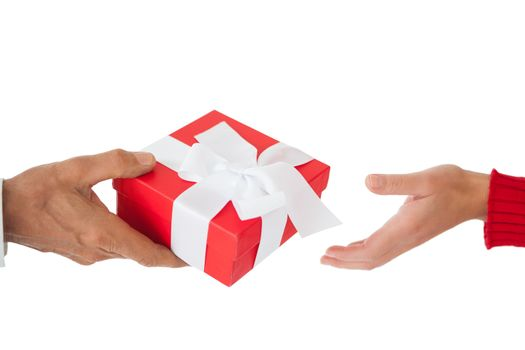 Couple passing a wrapped gift on white background